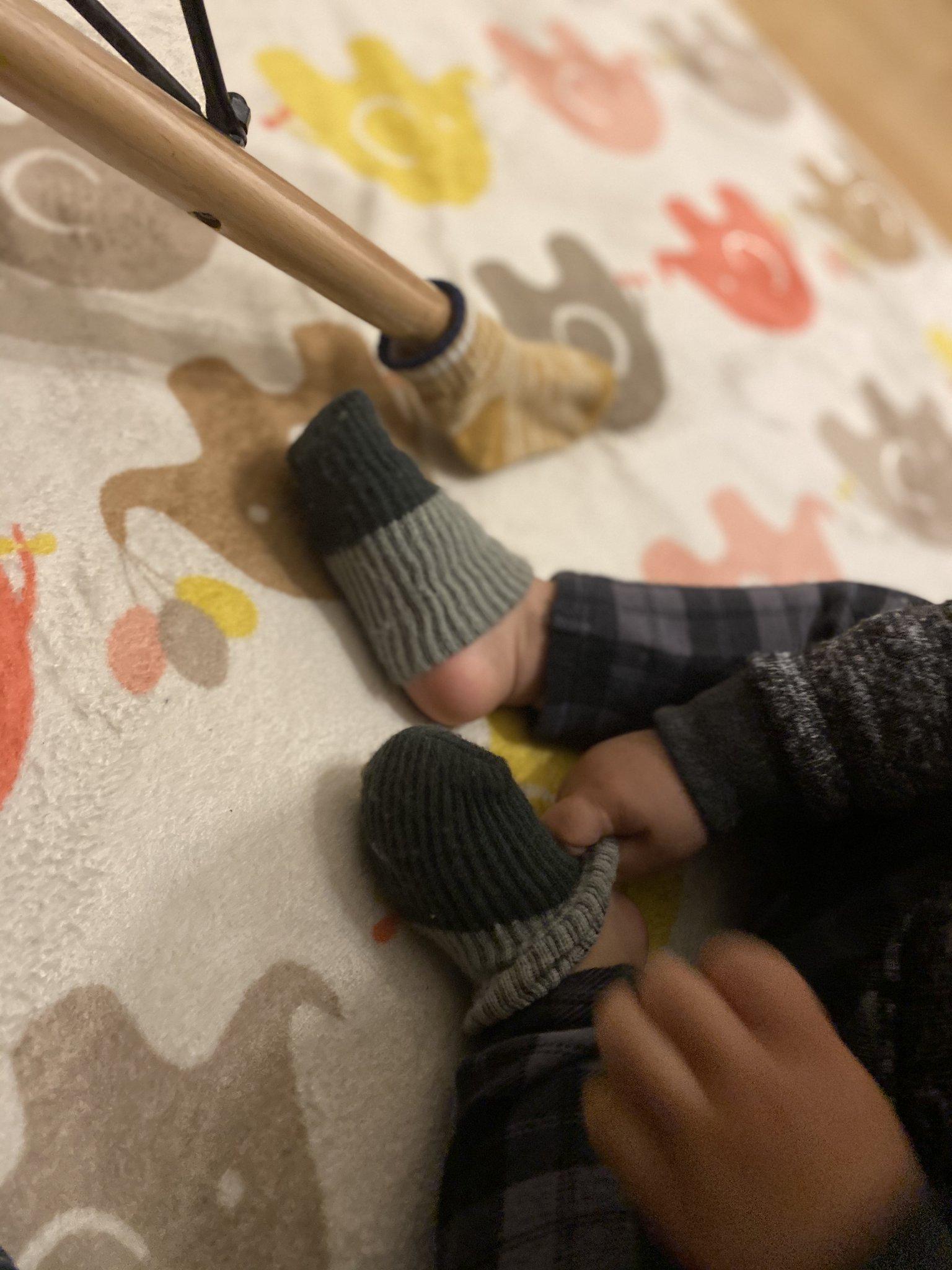 椅子と靴下を交換する2歳児
